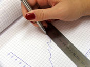 woman's hand making a chart on graph paper